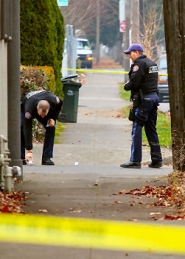 by: David F. Ashton Across the street from the Mitchell Court Apartments, officers place evidence markers over spent bullet shells on December 10th.
