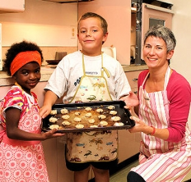 "by: David F. Ashton St. Agatha Catholic School preschooler Justine and fourth-grader Theo help their mom, Christine Pashley, editor of the newly-published book ""St. Agatha Centennial: Faith, Family & Food"", here with a batch of ""Ranger Cookies"", a recipe submitted by a former St. Agatha student of the Class of 1952 — now a Catholic nun."