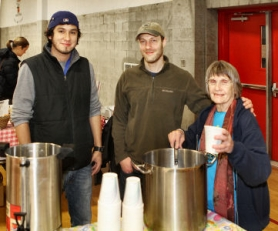 by: David F. Ashton Volunteers Sergio Luna and Carol Craig flank new Market Manager Adam Seidman, as they offer hot cider to shoppers at the Moreland Holiday Farmers Market.