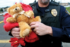 by: Jim Clark Gresham Traffic Officer David Snider holds  one of the bear and blanket gifts donated by the administrative staff of the Gresham-Barlow School District on Friday, Dec. 23.