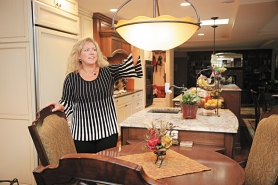 by: gail emmerson park West Linn interior designer Tamara Griffin straightens a lamp fixture hanging over the short end of a 186-inch-long island and dining table combination.