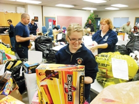 by: Photo courtesy of Forest Grove Fire & Rescue Forest Grove volunteer firefighter Liz Hinton, who coordinated the Forest Grove firefighters' toy drive this year, put the finishing touches on care packages last Wednesday.