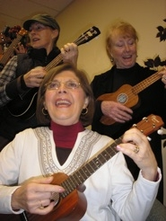 "by: ellen Spitaleri Monica Mumper, center, and sisters Laraine and Carol LaTourette, from left, sing and strum through a rendition of ""Kumbaya"" at the Milwaukie Center."