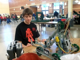 by: BOB TISCH Jess Wittrig, a Sandy High freshman, makes a last-minute modification to his team's robot at a league tournament in Salem Dec. 10.