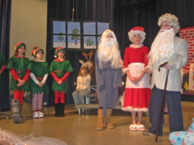 "by: Barbara Sherman WHERE'S THE RED SUIT? – In a quandary about where to find Santa's missing red suit in Deer Creek Elementary's holiday play, ""S.O.S. from Santa,"" are some of the student actors."