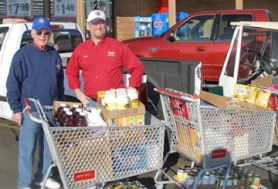 by: Paul Wilson LIONS GET AROUND — King City Lions Club member Bill Gerkin (left) stands with Grocery Outlet co-owner Tony Slyter after a shopping spree for West Coast Bank's food drive that resulted in a big donation to the Tigard Covenant Church food pantry.