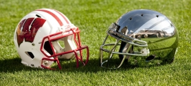 by: CHRISTOPHER ONSTOTT Oregon's new helmet (right) shines in the sun on the Rose Bowl field and alongside the traditional Wisconsin helmet.