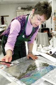 by: Jim Hart Leslie Cheney-Parr is seen at work in her studio on a monotype image. Among other printing techniques in the baker's dozen prints at the chamber's visitor center are linocuts, screen prints, carved woodblock printing, hand-colored relief prints and photo painting.