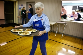 by: Jaime Valdez Jackie Deshaies, a volunteer at The Jesus Table, carries out the meal's entree to guests at Tuesday night's dinner in Cedar Mill Bible Church, 12208 N.W. Cornell Road.
