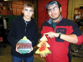 by: Contributed photo From right Chris Dahmen, a sophomore at Reynolds High School, and Jonathan Santiago, a senior, display ornaments they helped make for the holiday tree in Troutdale.