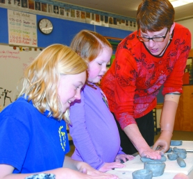 by: Christina Lent Lynn Whitehead shows second-grader Ella Deveaux and fifth-grader Schuyler Dull how to gently roll clay to make a pinch pot out of coils in her Cedar Mill Elementary School classroom.
