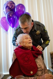 by: Jaime Valdez Washington County Sheriff Pat Garrett kisses Barbara White after commissioning her as an honorary deputy during her 100th birthday party on Friday.