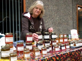 "by: Jim Hart Linda Smith-Heinrich of Boring arranges a display of her homemade ""Hot Dolly's Pepper Jelly"" at a recent market in Sandy. After a short hiatus, the market returns Feb. 4."