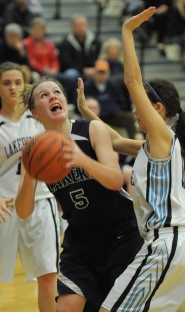 by: VERN UYETAKE Lake Oswego's Paige Timberg eyes the basket in the Laker girls' 61-52 victory over Lakeridge last Friday. Timber had a game-high 17 rebounds in the contest.
