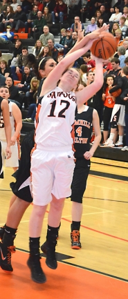 by: John Brewington REBOUNDING—Scappoose's Brittany Catlow pulls down a rebound with a defender on her back during last Friday's game.