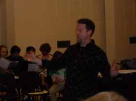 by: BARB RANDALL John Stuber, director of Lewis & Clark's Community Chorale, leads the choir through warm-up at a recent rehearsal for the (Anti) Valentine's Concert Feb. 10. Admission to the tongue-in-cheek performance is free.