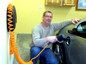 by: Jim Hart Sandy resident Scott Winneguth demonstrates how he connects his car's battery to a charging unit on the wall inside his garage.