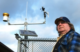 by: VERN UYETAKE Kevin McCaleb, the city's water conservation specialist, stands by one of Lake Oswego's weather stations, which track conditions such as rainfall, air temperature, wind speed and direction and more.