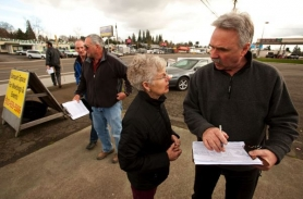 by: Christopher Onstott Punky Scott, left, owner of The Bomber Restuarant talks with Steven Bebb about signing a petition that will give Clackamas County residents an opportunity to vote on TriMet's light-rail expansion into Milwaukie at a booth along McLoughlin Boulevard.