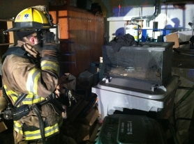 by: submitted photo A TVF&R firefighter examines a terrarium after rescuing a 5-foot king snake from the damaged home.