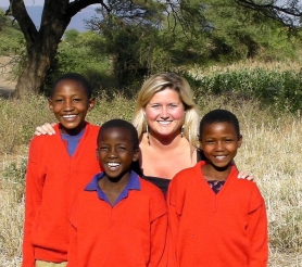 "by: SUBMITTED PHOTO Ashley Holmer and three of her students in the Red Sweater Project start the day with big smiles at their school in Tanzania. Holmer said she was ""crazy enough to say 'yes'"" when asked to begin a secondary school in 2005. She is now starting another school."