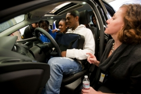 by: CHRISTOPHER ONSTOTT Benson High School students Dodji Ketevi (center, from left), Angela Durns and Twaun White check out the inside of a new 2012 Ford Focus on Monday during a visit by Ford engineers including Jennifer Brace (right). Ford visited Benson's auto shop to engage and inspire students pursuing careers in design and manufacturing.