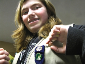 by: Sara Hottman Boring Middle School student Hailey Marino, 12, shows off her bronze pin, the highest award available to Junior-level Girl Scouts. She plans on earning the top Girl Scout honor: the gold pin.