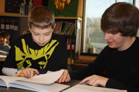 by: Lori Hall Sophomore Connor Gardner, right, helped second-grader Austin Hart with his lion story March 16.