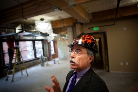 by: CHRISTOPHER ONSTOTT Michael Gaeta, president and CEO of the Oregon College of Oriental Medicine, tours his school's future home in the renovated Globe Hotel. Gaeta, a dedicated Harley rider, received the decorated hard hat as a gift from his wife.