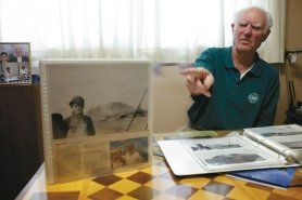 "by: Jaime Valdez Harlan ""Hal"" Roth points to a picture of himself on a naval ship with Iwo Jima's Mount Suribachi in the background during World War II. He later went to that same location on a cruise and had someone take a picture of himself and his, Garnice, with him holding the picture."