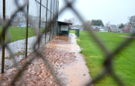 by: John Brewington A LITTLE WET—The Scappoose High ball field looked a little more conducive to swimming laps than playing baseball on Friday. Coach Robert Medley said draining the wet outfield is the biggest problem facing the Tribe.
