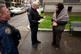 by: CHRISTOPHER ONSTOTT Portland Police officer Christopher Burley (center), with partner Brian Dale, talk about a possible violation with a man in Old Town. In May, homeless people picked up on minor charges will be referred to a new community court at the Bud Clark Commons.