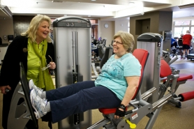 by: Jaime Valdez Elsie Stuhr Center Supervisor Linda Jo Enger talks with Hillary Smith of Raleigh Hills during her workout. Smith has already forgotten what the old fitness room at the center looked like.