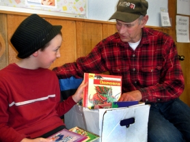 by: Jim Hart Mitchell Baca, 9, discusses a favorite book with his grandfather, Dale Hauff of Sandy, a member of the Friends of the Sandy Public Library who is raising his grandson and teaching him the importance of reading.