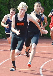 by: John Brewington, Scappoose's Michael Shoun takes a handoff from Carson Davison for the anchor leg of the 4x100 relay. The Indians won both relays and seven events overall in the meet.