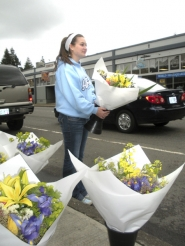 by: Jim Hart, Standing at the edge of Pioneer Boulevard, Shelby Jones of Sandy promotes flower sales at Sandy's First Saturday Market for flower business owner Mary Cha of Damascus, not pictured. The June 2 market will move to the City Hall parking lot adjacent to Meinig Park.