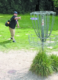 by: Katie Wilson, Nicholas Somppi, of Vancouver, Wash., throws his disc home into a metal score basket at a disc golf course May 18 at St. Johns' Pier Park. A group of Portland disc golfers recently submitted a proposal to install a similar style course at McCormick Park in St.Helens.