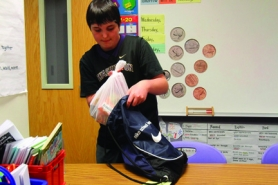 by: Jonathan House, At William Walker Elementary School, Ethan McCanta takes donated food and puts it into backpacks that less-fortunate students will take home with them the next school day.