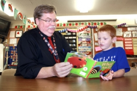 by: Lisa K. Anderson, Pat Sanders, retiring Kelso Elementary principal, has loved reading with students such as kindergartner Max Nickila, 6. Instead of being afraid of the principal's office, kids at Kelso often ask to visit Sanders for fun, reading to him and telling him stories about their families.