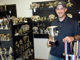 by: Jim Hart, Grant Baker stands in the middle of some of the trophies and other awards that adorn the shelves of his shop in Sandy. Baker took over the business when the previous owner retired, and he plans to expand its offerings.