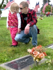 by: Jim Hart, Memorial Day isn't just for veterans; it's to remember all the departed. At graveside in Fir Hill Cemetery, Mathias Engblom of Sandy talks to his 3-year-old daughter, Lilian, about the life of Jeffrey Flood, uncle to Engblom's wife, Candi Jo Barbre.