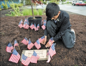by: Chase Allgood, Erick Macias, a fourth grader at Echo Shaw Elementary School, plants a miniature flag next to a Japanese Maple tree planted in memory of fallen serviceman Ryley Gallinger-Long.