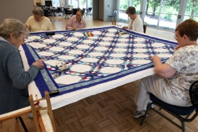 by: Jaime Valdez, Members of the Tualatin Quilters spend an afternoon working on a raffle quilt at the Juanita Pohl Center.