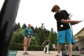 by: Jaime Valdez, Tyler Shannon, 15, swings at a golf ball with his mentor Cody Everett. A new program hopes to add more mentors in Tigard and Tualatin this year.