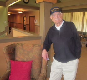 by: Barbara Sherman, WAR MOMENTO — Bob Young, standing in the Summerfield Clubhouse, wears his
