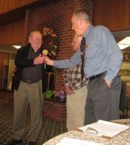 by: Barbara Sherman, VOLUNTEERS RULE – Tigard Senior Center Director Jay Gilbertson (right) hands the microphone to Forrest Masters while Bill Gerkin looks on during the program honoring volunteers.