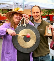 by: David F. Ashton, By sounding her gong, volunteer Mary Magdic signals the opening of the 2012 season of the Moreland Farmers Market as manager Adam Seidman rings the ceremonial cowbell.