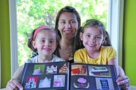 by: sUBMitted photo, Nohora Lambert, with her daughters, holds a photo book of her cakes.