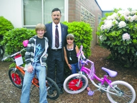 by: Susie Werner, Winners of the Books for Bikes drawing at Gaffney Lane Elementary School were sixth grade student Logan Endicott and Aviana Palaoro, a second grader. Mike Churchill, middle, represents the Oregon City Masonic Lodge, the sponsor of the event.