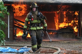 by: Jonathan House, TVF&R firefighter Todd Herrington picks up tools during a practice burn in Tigard on Thursday.